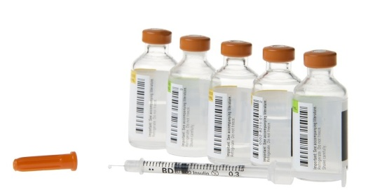 Med bottles lined in row with syringe single drop fluid