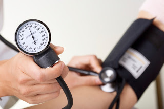 Doctor/nurse checking blood pressure with sphygmomanometer gauge in focus.