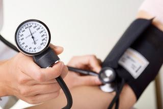 Doctor/nurse checking blood pressure with sphygmomanometer gauge in focus.