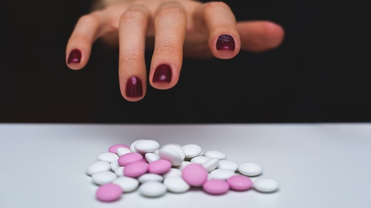 hand-reach-drugs-pink-opioids-pills